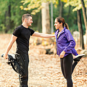 Happy couple exercising in park