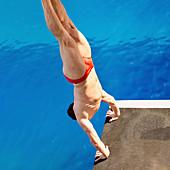 Male diver in handstand on diving platform