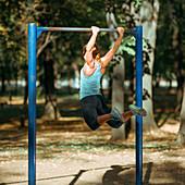 Woman exercising on outdoor horizontal bar