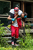 Rescue worker evacuating woman from house