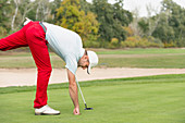 Golfer taking ball from hole