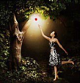 Woman reaching for glowing apple, illustration