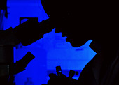 Silhouette of a person using a microscope