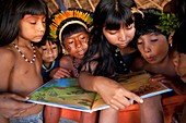 Xingu children reading a book, Brazil