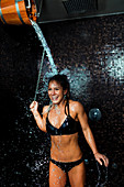 Woman under ice cold shower bucket