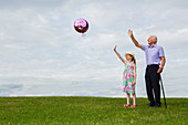 Grandfather and granddaughter releasing a balloon