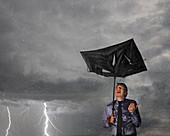 Businessman with broken umbrella in a storm