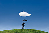 Businessman holding umbrella underneath a single cloud