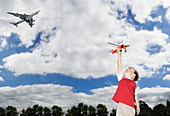 Boy playing with toy plane with plane flying overhead