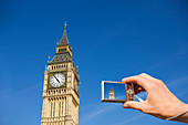 Tourist photographing Elizabeth Tower, London, UK