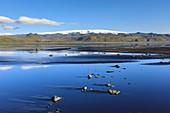Myrdalsjoekull reflected in tidal flat,Iceland