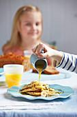 Kokosnuss-Bananen-Pancakes mit Sauce begiessen