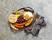 Colombian bandeja paisa, chicharrón (fried pork belly), sausage, arepa, beans, fried plantain, avocado egg, and rice