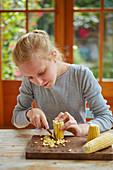 Mädchen schneidet Maiskörner vom Maiskolben