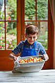Junge hält Backform mit gebratenem Blumenkohl und Kürbis