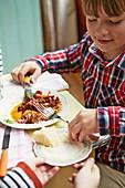 Kleiner Junge isst Pasta mit Pulled Beef Ragout