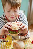 Boy eating green burgers