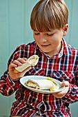 Boy eating fish finger wraps