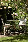 Sitzplatz neben Kletterrose und Rosenstrauß auf dem Tisch