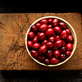 Cranberries in bowl on wooden cutting board