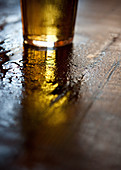 A glass of beer on a wet wooden table