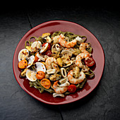 Mediteranian seafood, white wine, shrimp, mussels, clams, calamari, tomatoes in plate on black