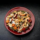 Mediteranian seafood, white wine, shrimp, mussels, clams, calamari, tomatoes in plate on black