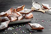 Muzen (German Karneval pastries) with icing sugar and confetti