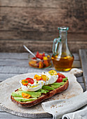 A baguette topped with avocado and burrata