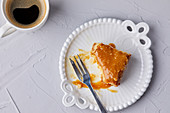 Half eaten slice of Tres Leches cake, covered with caramel sauce and sprinkled with sea salt