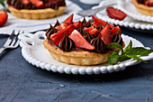 Mini tart with strawberry jam, served with fresh strawberries and chocolate ganache