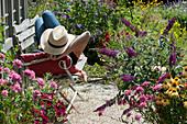 Frau relaxed auf Bank auf Kiesterrasse am Gartenhaus