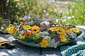 Windlicht in Kranz aus Ringelblumen, Schafgarbe, Salbei, Oreganoblüten und Wicke als Tischdekoration