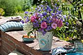 Sommerstrauß aus Glockenblumen, Rosen, Hortensie und Spornblume auf Gartenmauer