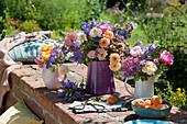 Bunte Sommersträuße aus Rosen, Storchschnabel, Glockenblumen, Spornblumen und Oreganoblüten auf Gartenmauer