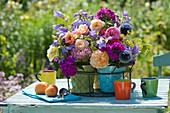 Sträuße aus Rosen, Flammenblume, Glockenblume, Kugeldistel und Fenchelblüte im Drahtkorb