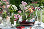 Kleine Sträuße aus Rosenblüten und großer Bibernelle in Flaschen als Tischdeko, rote Johannisbeeren