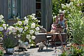 Sommerterrasse mit weißen Hortensien, Pfahlrohr und Eisenkraut, Frau sitzt im Korbsessel, Hund Zula im Schatten