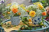 Kleine Sträuße aus Rosen, wilder Möhre, Fenchel und Wiesenkümmel in Kaffeetassen, Zweige mit Stachelbeeren als Deko