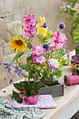 Sträuße mit Gladiolen, Sonnenblume, Kugeldistel, Waldrebe, Dahlie, Fenchelblüte und Wiesenkümmel in Holzkistchen