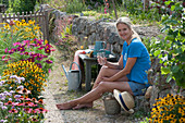 Frau genießt den Sommer am blühenden Beet