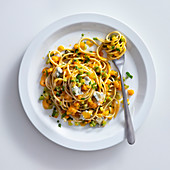 Spaghetti with pumpkin and gorgonzola cooked in a wok