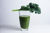 Fresh kale leaf and a glass of green juice