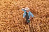 Aerial view of farmer standing in wheat field