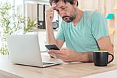 Man receiving upsetting text message