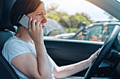 Woman driving car and using phone