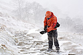 Man in snow storm, Lake District, UK