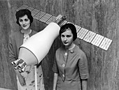NASA scientists with a model of a Pegasus satellite, 1964