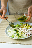 Dressing being added to mushroom salad with fennel