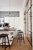 Zeitgenössische Küche in Weiß-Schwarz abgetrennt vom Wohnbereich durch raumhohe Glaswand